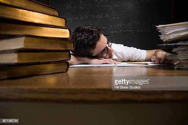 Nerdy man sleeping on school desk