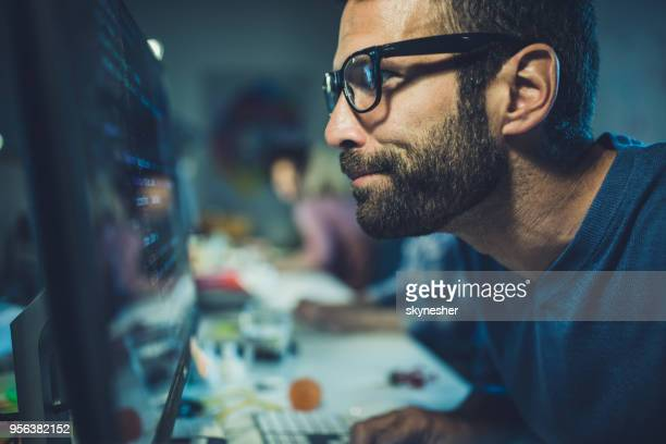 nerdy programmer analyzing codes on desktop pc in the office. - nerd stock pictures, royalty-free photos & images