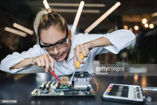 Nerdy student making an effort while trying to repair mother board.