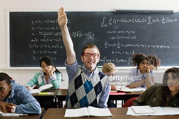 nerdy student with hand raised - ebete foto e immagini stock