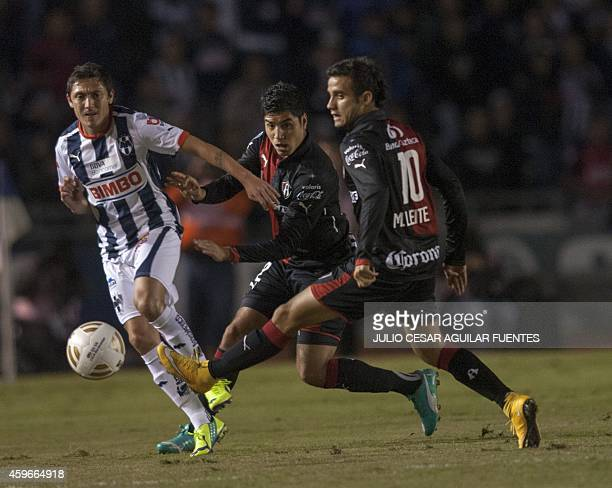 Neri Cardozo of Monterrey and Maikon Leite and Luis Venegas of Atlas vie for the ball during their quarterfinal football match of the 2014 Mexican...