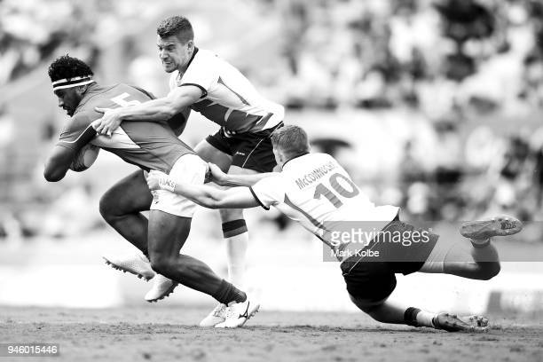 Neria Fomai of Samoa is tackled by Tom Mitchell and Ruaridh McConnochie of England during the Rugby Sevens match between England and Samoa on day 10...