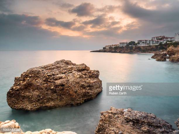 nerja town and a rock in the coast - costa del sol stock photos and pictures