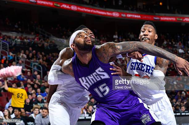 Nerlens Noel and Robert Covington of the Philadelphia 76ers battle against DeMarcus Cousins of the Sacramento Kings at the Wells Fargo Center on...