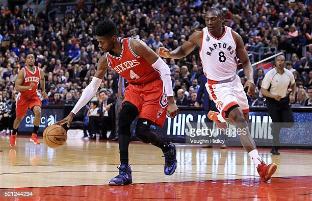 Nerlens Noel of the Philadelphia 76ers dribbles the ball as Bismack Biyombo of the Toronto Raptors defends during the first half of an NBA game at...
