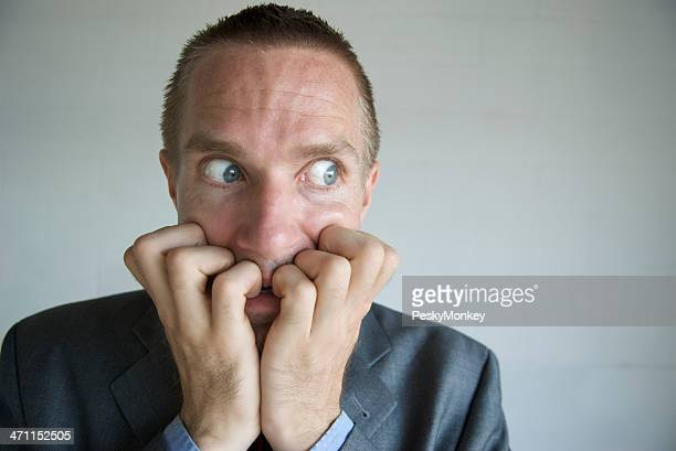 Nervous Businessman Biting Fingers with Wide Eyes