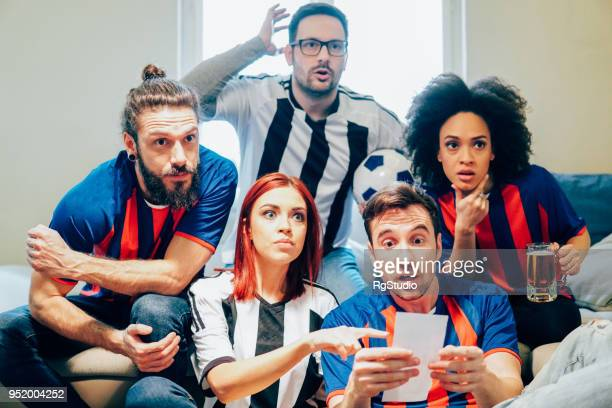 Nervous group of soccer fans looking at betting slip