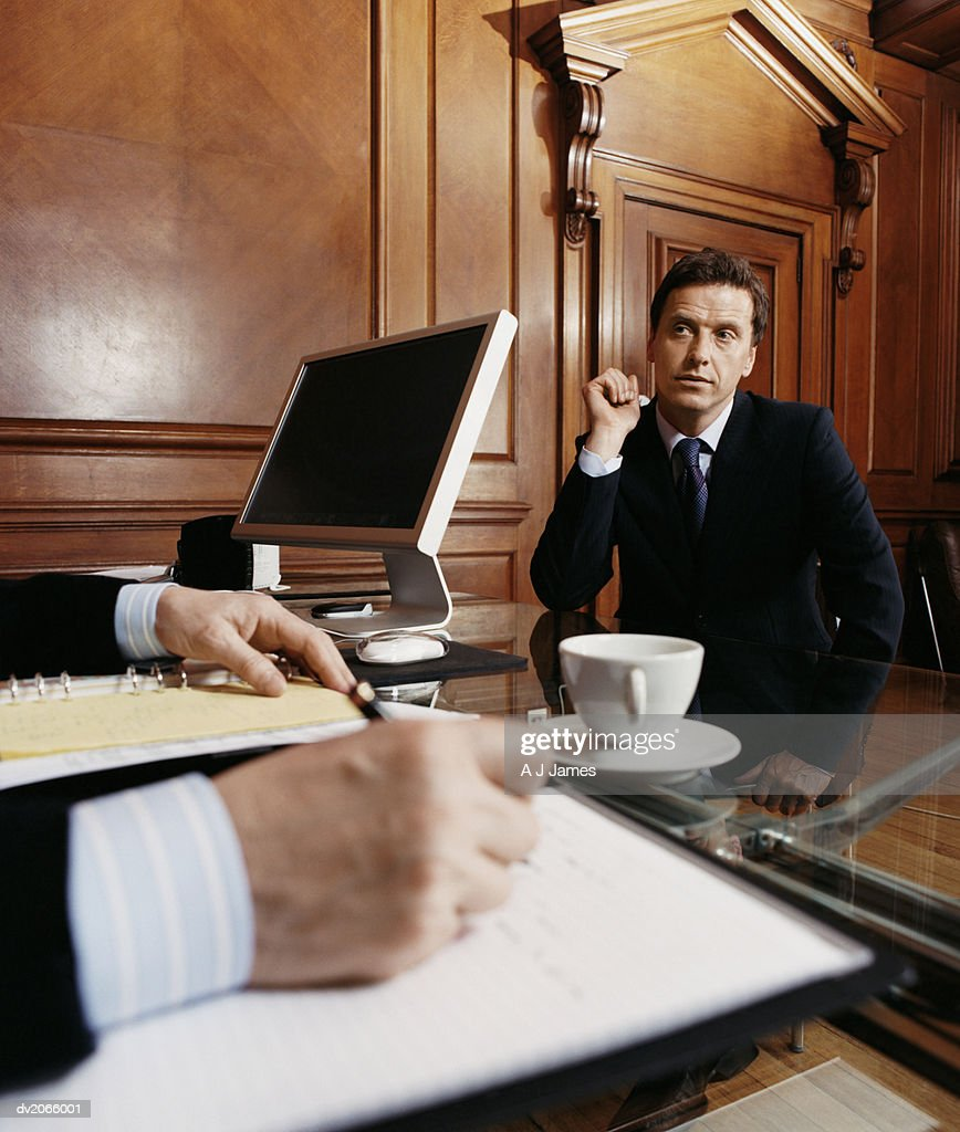 Nervous Looking Businessman Sitting at a Desk, Other Businessman Taking Notes : Stock Photo