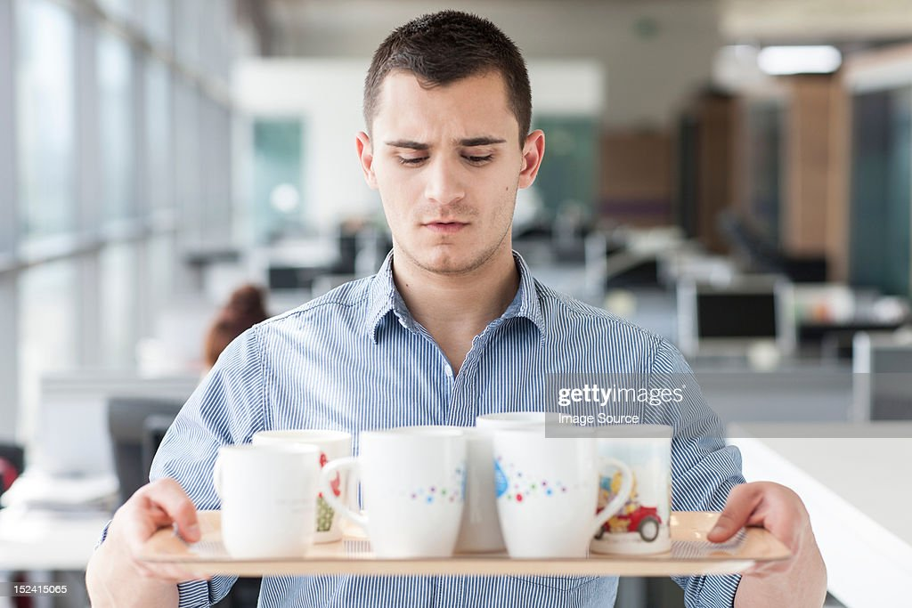 Nervous looking man carrying tray of mugs : Stock-Foto
