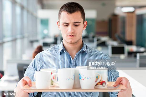 nervous looking man carrying tray of mugs - day 1 stock pictures, royalty-free photos & images