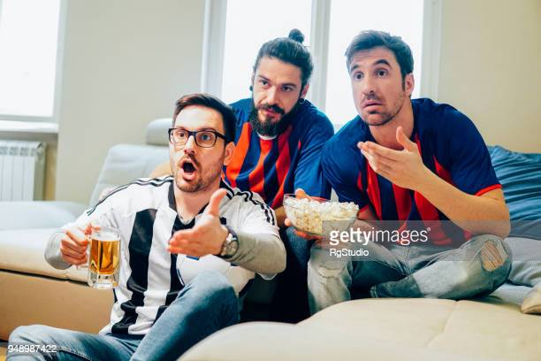 Nervous male football supporters drinking beer and eating popcorn
