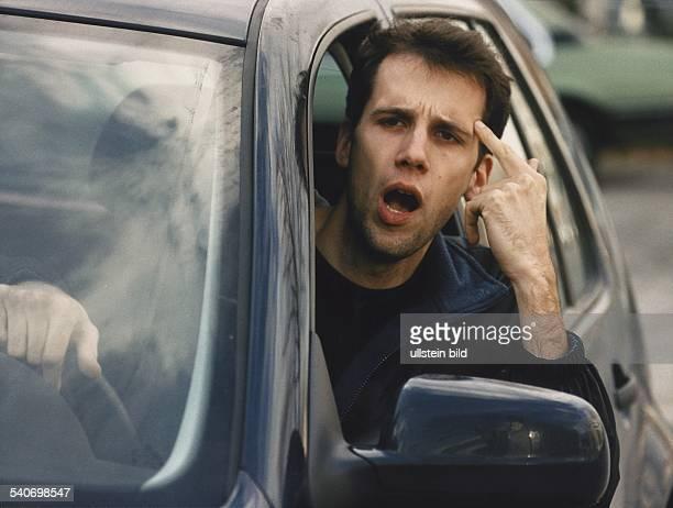 Nervöser Autofahrer tippt sich mit dem Zeigefinger an die Stirn. Aggression; Aggressivität; Mann; Nervosität; Straßenverkehr; Verkehrsverhalten;...