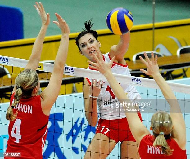 Neslihan Darnel of Turkey spikes the ball over Tammy Louise Mahon and Jennifer Hinze of Canada during their first round match at the World Women's...