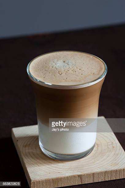 Nespresso machine and coffee latte on a wooden tab