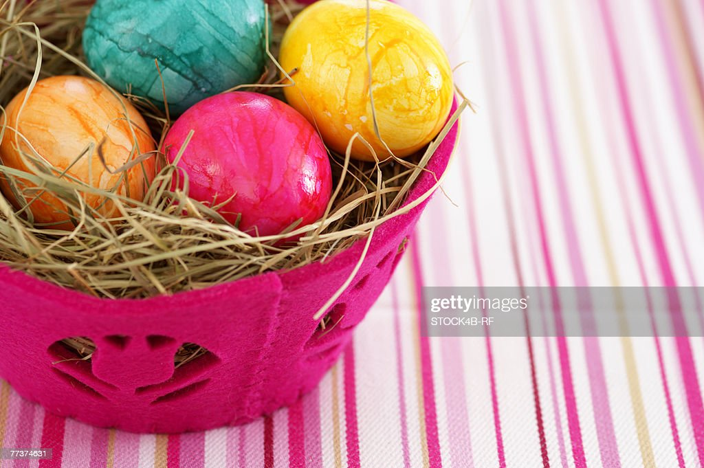 Nest made of straw with eggs in a basket, close-up : Photo