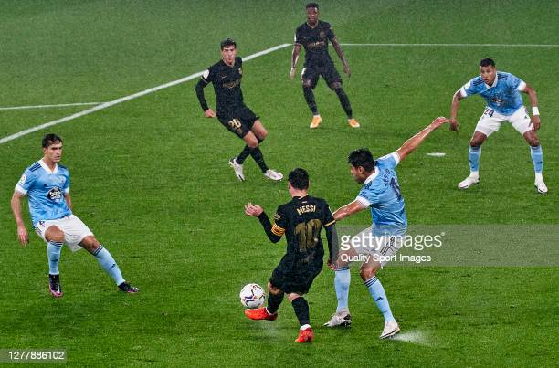 Nestor Araujo of Celta de Vigo competes for the ball with Lionel Messi of FC Barcelona during the La Liga Santander match between RC Celta and FC...