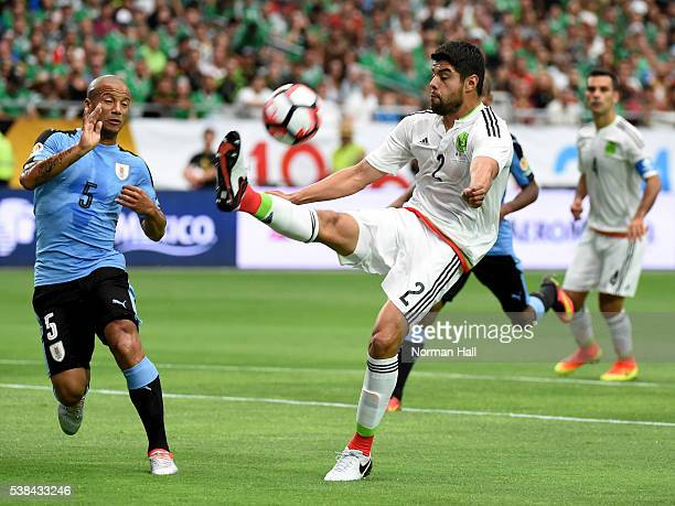Nestor Araujo of Mexico kicks the ball up field while Carlos Sanchez of Uruguay defends during the first half of a group C match at University of...