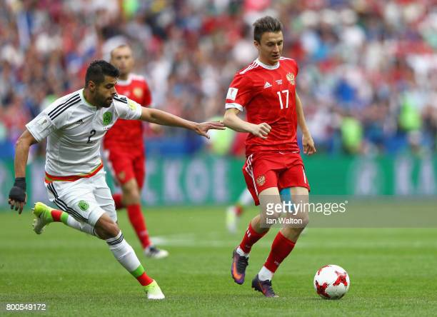 Nestor Araujo of Mexico puts pressure on Aleksandr Golovin of Russia during the FIFA Confederations Cup Russia 2017 Group A match between Mexico and...