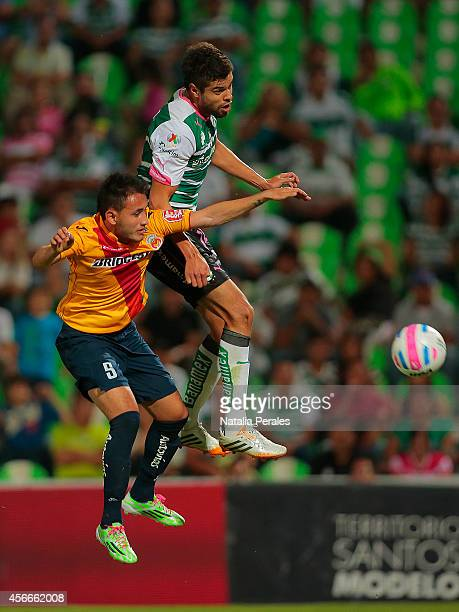 Nestor Araujo of Santos and Carlos Guzman of Morelia jump for the ball during a match between Santos Laguna and Morelia as part of 12th round...