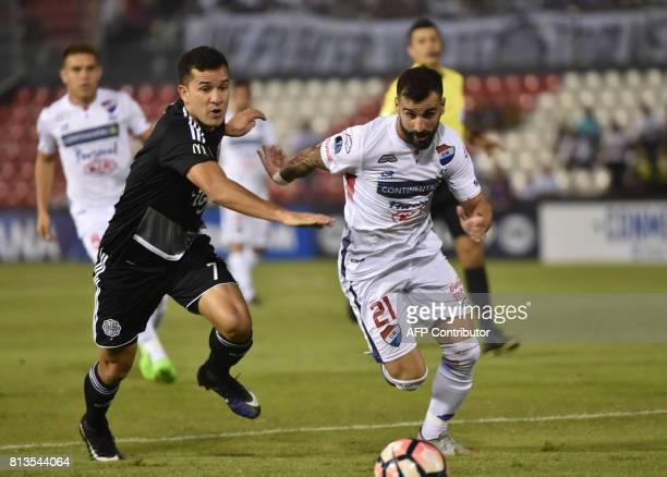 Nestor Camacho of Paraguays Olimpia vies for the ball with Rodrigo Rojo of Paraguay's Nacional during their 2017 Copa Sudamericana football match at...