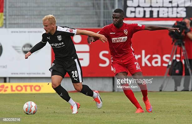 Nestor Djengoue of Cottbus battles for the ball with Soeren Bertram of Halle during the third league match between FC Energie Cottbus and Hallescher...