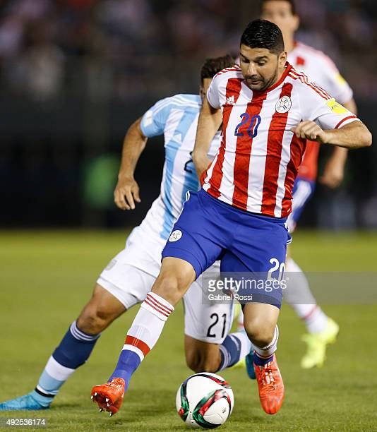 Nestor Ortigoza of Paraguay drives the ball followed by Emmanuel Mas of Argentina during a match between Paraguay and Argentina as part of FIFA 2018...