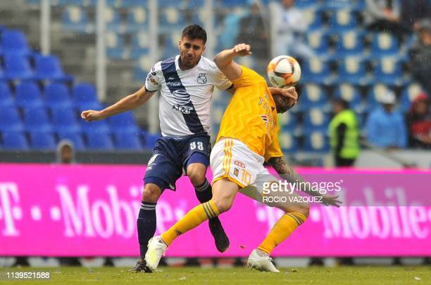 Nestor Vidrio of Puebla vies for the ball with French Andre-Pierre Gignac of Tigres during a Mexican Clausura 2019 tournament football match at the...