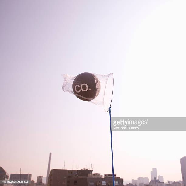 net catching carbon dioxide molecule over city at dusk - carbon dioxide stock pictures, royalty-free photos & images