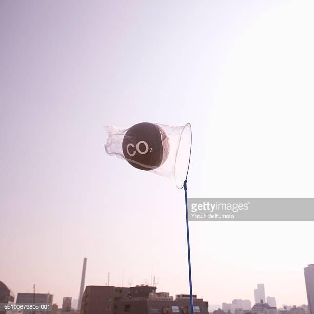 net catching carbon dioxide molecule over city at dusk - carbon dioxide bildbanksfoton och bilder