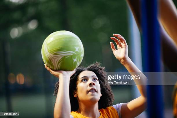 netball player about to take shot at goal at outdoor sports court in park - flick stock pictures, royalty-free photos & images