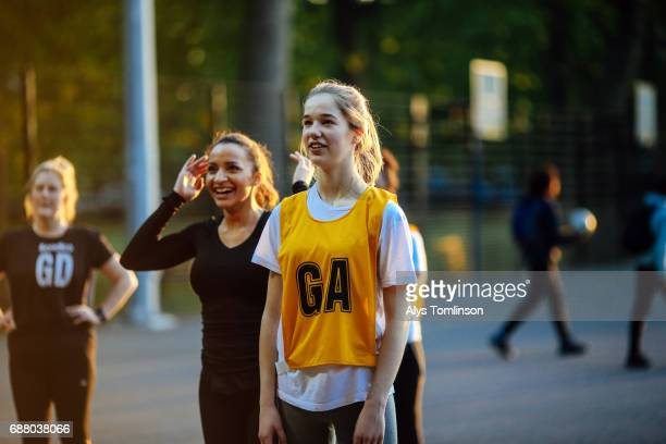 netball players in match looking to goalpost