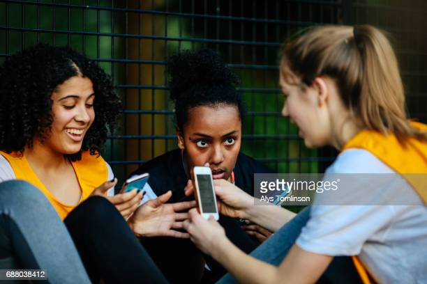 netball team looking at their phones on sidelines of outdoor court