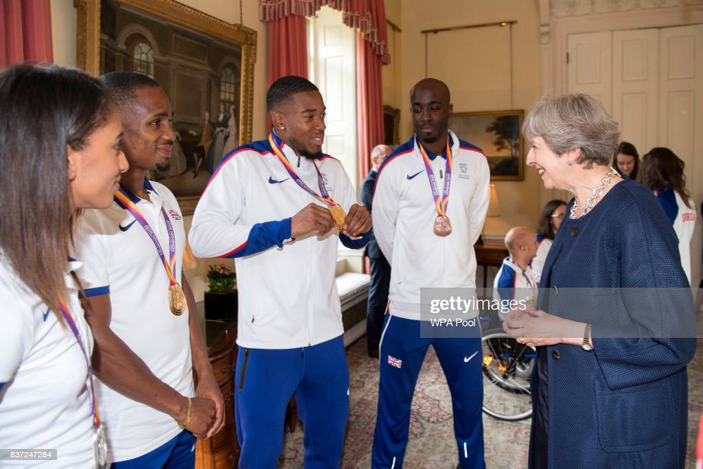 Nethaneel Mitchell-Blake shows his Gold medal for winning 4x100 metre relay to British Prime Minister Theresa May a reception for who competed in the World Athletics Championships and World Para Athletics at 10 Downing Street on August 22, 2017 in London, England.