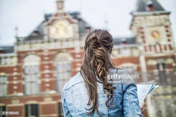 Netherlands, Amsterdam, back view of woman with city map in front of central station