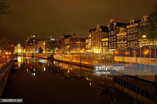 Netherlands, Amsterdam, Bloemenmarkt and canal, night