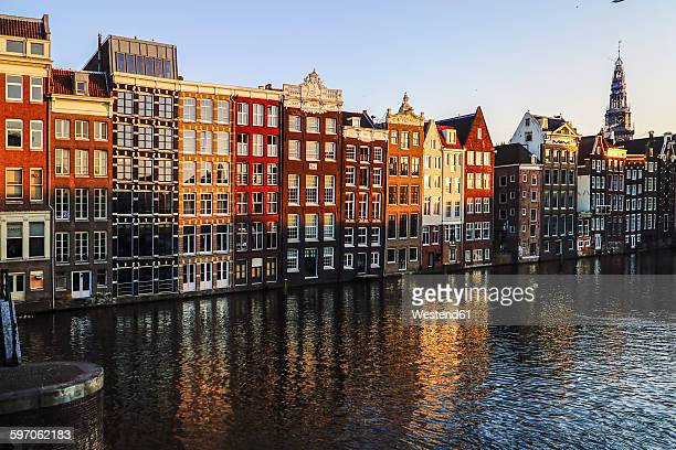 netherlands, amsterdam, damrak, view to row of canal houses in the old town - ámsterdam fotografías e imágenes de stock