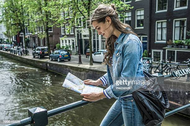 Netherlands, Amsterdam, female tourist looking at city map in front of town canal