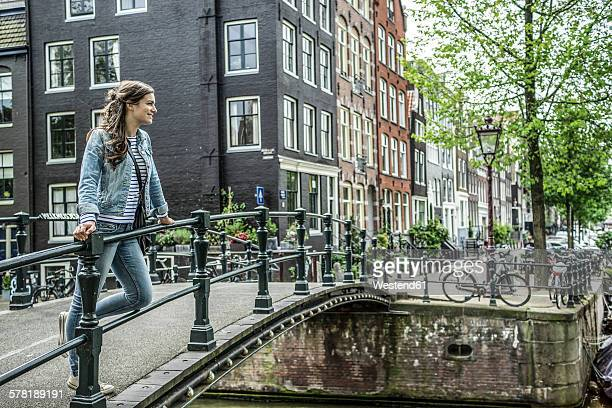 Netherlands, Amsterdam, female tourist standing on footbridge