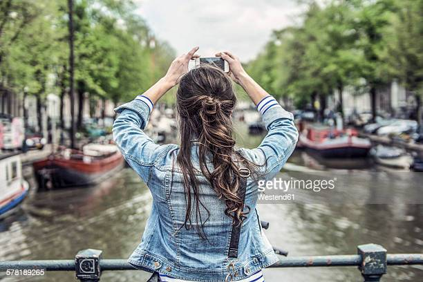 Netherlands, Amsterdam, female tourist taking a selfie with smartphone