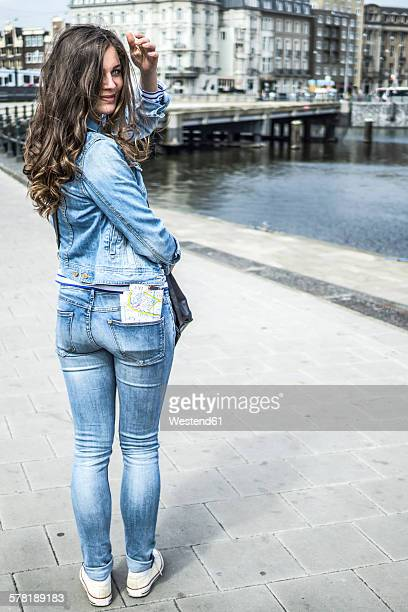 Netherlands, Amsterdam, female tourist with city map in her trouser pocket