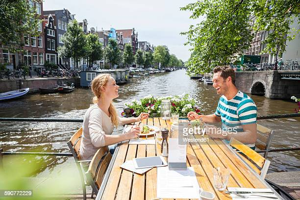 Netherlands, Amsterdam, happy couple having lunch at town canal