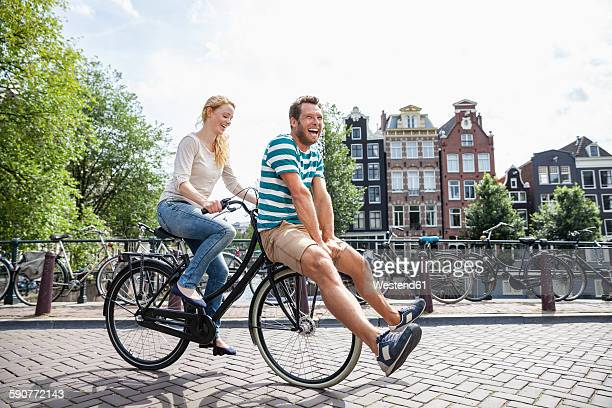 Netherlands, Amsterdam, happy couple riding bicycle in the city