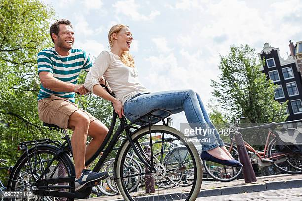 netherlands, amsterdam, happy couple riding bicycle in the city - mid adult couple stock pictures, royalty-free photos & images