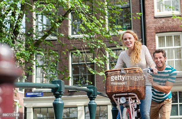 Netherlands, Amsterdam, happy couple with bicycle in the city