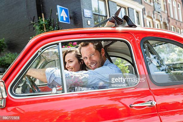 Netherlands, Amsterdam, happy couple with small car in the city