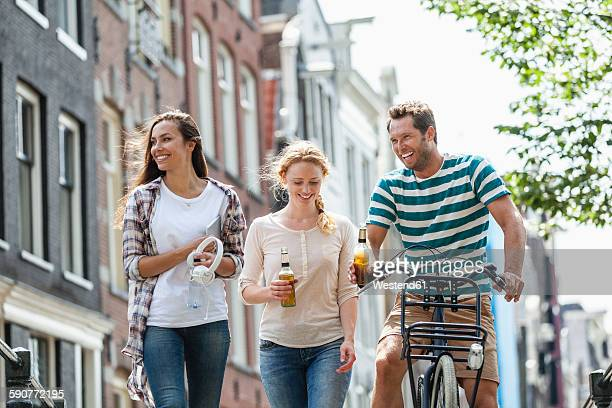 Netherlands, Amsterdam, happy friends with beer bottles and bicycle in the city