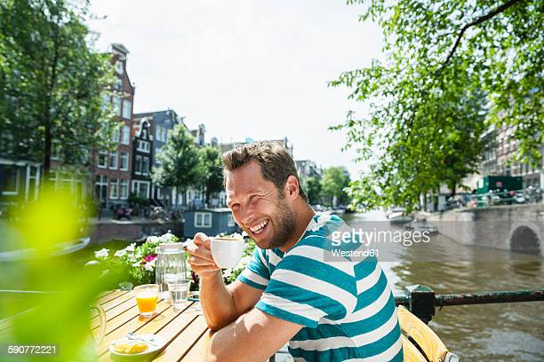 Netherlands, Amsterdam, happy man drinking cup of coffee at town canal