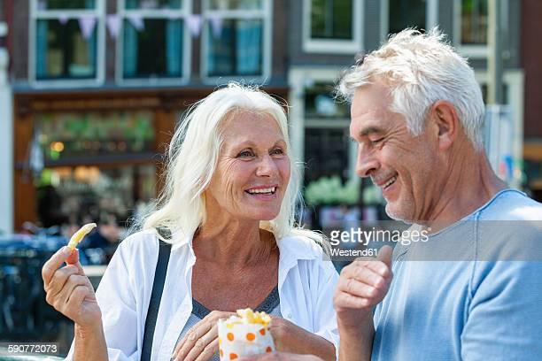 Netherlands, Amsterdam, happy senior couple eating French Fries