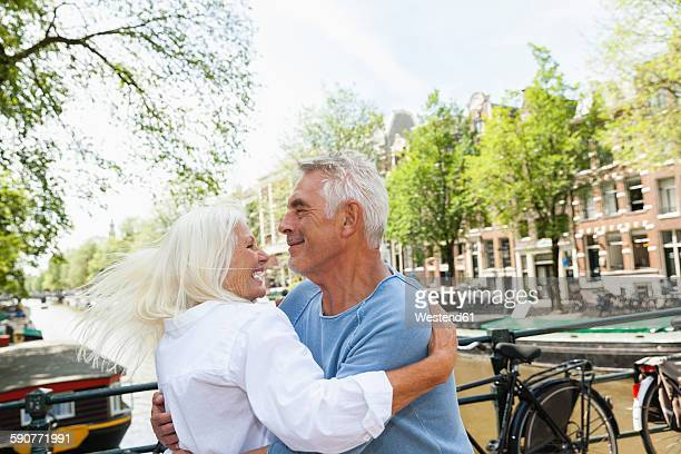 Netherlands, Amsterdam, happy senior couple hugging at town canal