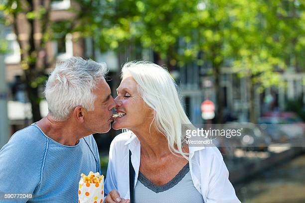 Netherlands, Amsterdam, happy senior couple sharing French Fries